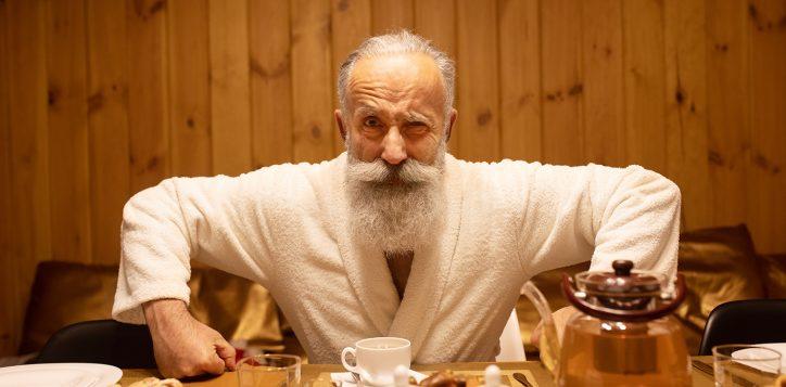 bearded-senior-man-drink-tea-after-procedure-sauna-concept-healthy-lifestyle