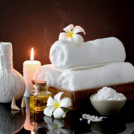 close up view spa treatment accessories with white towel candle aroma oil