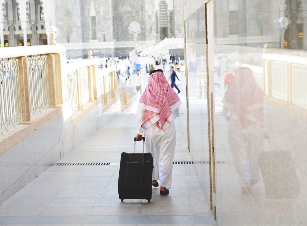 Arabic businessman walking with a suitcase